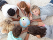 Group of teenagers on the floor examining a terrestrial world an