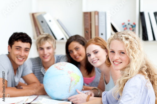 Smiling teenagers in a library working with a terrestrial globe