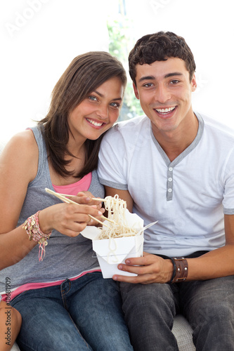 Smiling couple of teenagers eating pasta