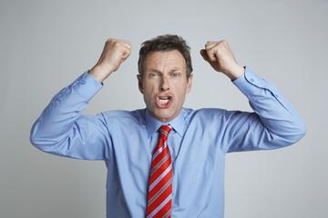 Studio shot of businessman shaking his fists