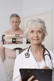 Senior medical practitioner stands with clip-board
