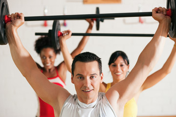Group with barbell in gym