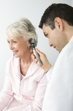 Mid adult doctor examining senior patient