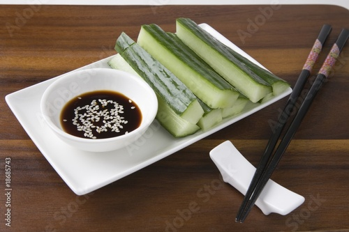 Soy sauce, cucumber and sesame seeds with chopsticks