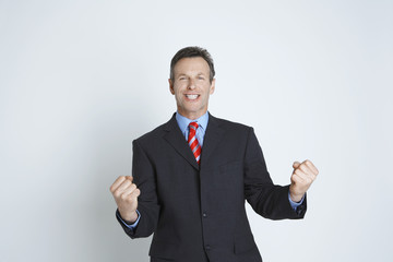 Studio portrait of businessman smiling and punching air