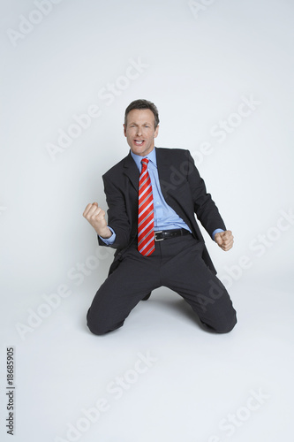 Studio portrait of businessman kneeling and punching air