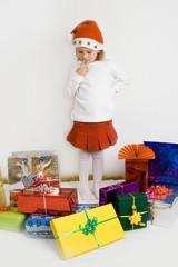 Mädchen mit Weihnachtsmannmütze und Geschenken