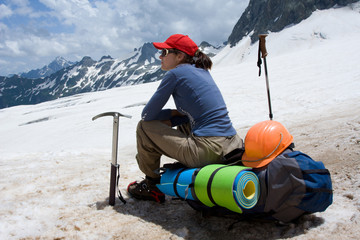 alpinist woman sitting on her backpack
