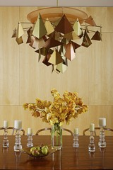 Metalworked light above centrepiece of cut flowers on table