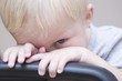 Blonde toddler peeks over chair, looking at camera