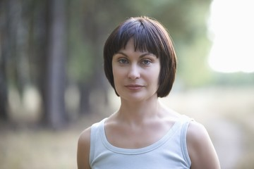 Mid adult woman stares directly at camera, portrait