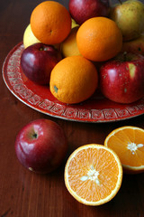 Apples and oranges on a red plate