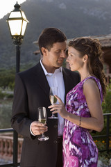 Well-dressed couple hugging and drinking champagne on balcony