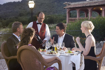 Waiter presenting wine bottle to well-dressed couples at table on restaurant balcony
