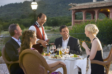 Waiter pouring wine for well-dressed couples at table on restaurant balcony