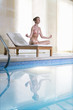 Woman meditating in lotus pose on lounge chair at poolside