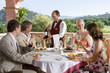 Waiter presenting wine to well-dressed couples at table on restaurant balcony