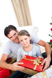 Smiling little girl with her father holding a Christmas gift