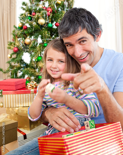 Father and little girl playing with Christmas presents