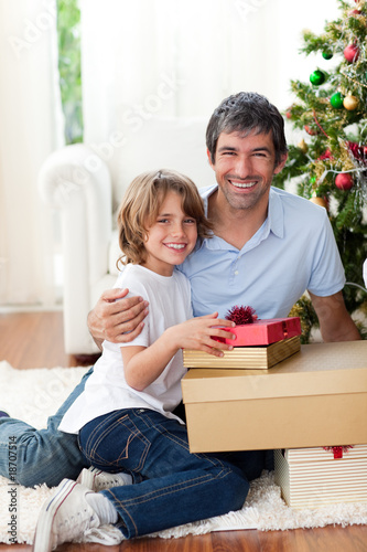 Father and his son holding Christmas gifts