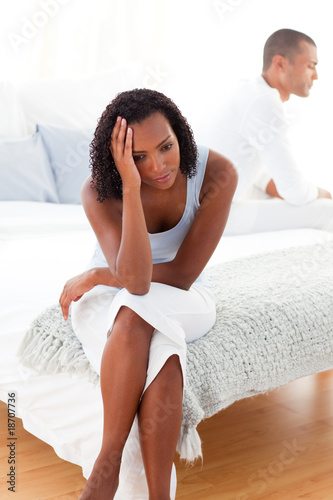 Angry couple sitting on bed separately