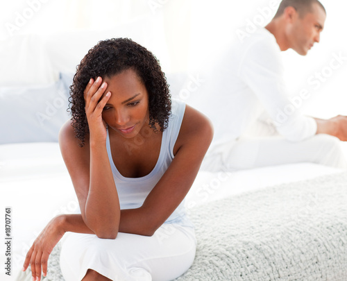 Upset couple sitting on bed separately