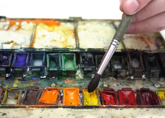 man's hand with paintbrush in over well-used watercolor paintbox