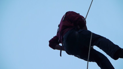 A Young man climbing to the top controls the rope