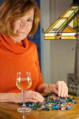 middleaged redheaded woman examining jewel beads
