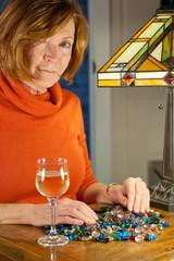 middleaged redheaded woman examining jewel beads