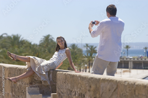 Man photographing woman on sunny ledge