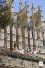 Man photographing woman on ledge