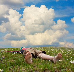 Hiker lies on the meadow