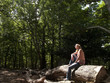Woman relaxing on log in sunny forest