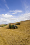 Tractors spreading fertilizer in sunny rural field