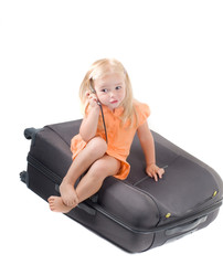 Little girl and suitcase in studio