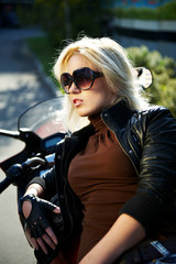 The girl the blonde in points at a stylish motorcycle