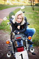 The girl the blonde on a stylish motorcycle