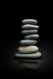 Tas de galets zen sur fond noir, empilage de pierres, équilibre