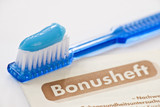 toothbrush with blue toothpaste and german bonusheft booklet poster