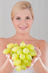 Young healthy woman with white grapes