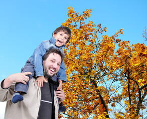 Happy father and his son on the back, fall