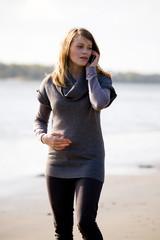 Frau telefoniert mit Mobiltelefon am Strand