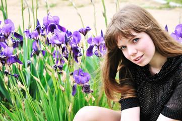 beautiful model sitting next to flowers