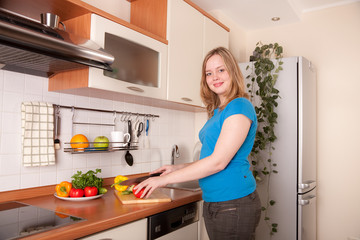 Beautiful woman cuts fresh vegetables in the kitchen