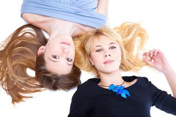 Two girls is lying on a floor. Isolated on the white background