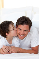 Little boy kissing his father lying on bed