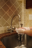 Hand washing and rinsing soapy water at a sink poster