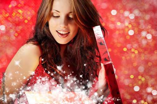 sexy girl smiles and holding a magic gift in packing