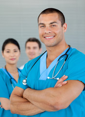 Portrait of an attractive doctor with his colleagues in the back